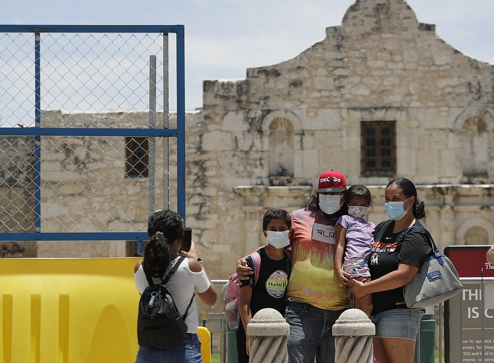 Visitors wearing masks to protect against the spread of COVID-19 pose for photos at the Alamo, which remains closed, in San Antonio, Wednesday, June 24, 2020. Cases of COVID-19 have spiked in Texas and the governor of Texas is encouraging people to wear masks in public and stay home if possible. (AP Photo/Eric Gay)