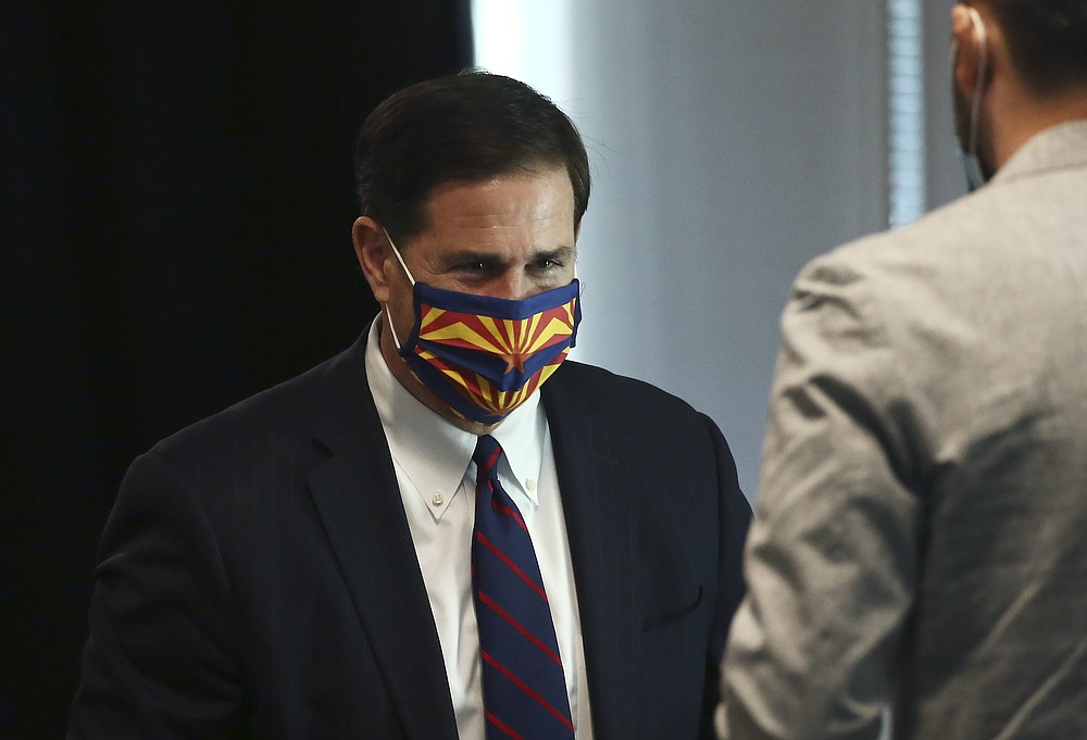 Arizona Gov. Doug Ducey wears a face covering due to the coronavirus at a news conference Wednesday, June 24, 2020, in Phoenix. (AP Photo/Ross D. Franklin)