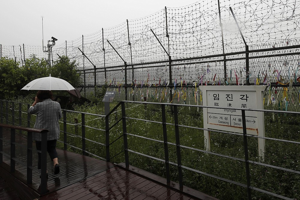 A woman walks in front of a directional sign showing the distance to North Korea's Kaesong city and South Korea's capital Seoul near the wire fences decorated with ribbons written with messages wishing for the reunification of the two Koreas at the Imjingak Pavilion in Paju, South Korea, Wednesday, June 24, 2020. North Korea said Wednesday leader Kim Jong Un suspended a planned military retaliation against South Korea, possibly slowing the pressure campaign it has waged against its rival amid stalled nuclear negotiations with the Trump administration. (AP Photo/Lee Jin-man)