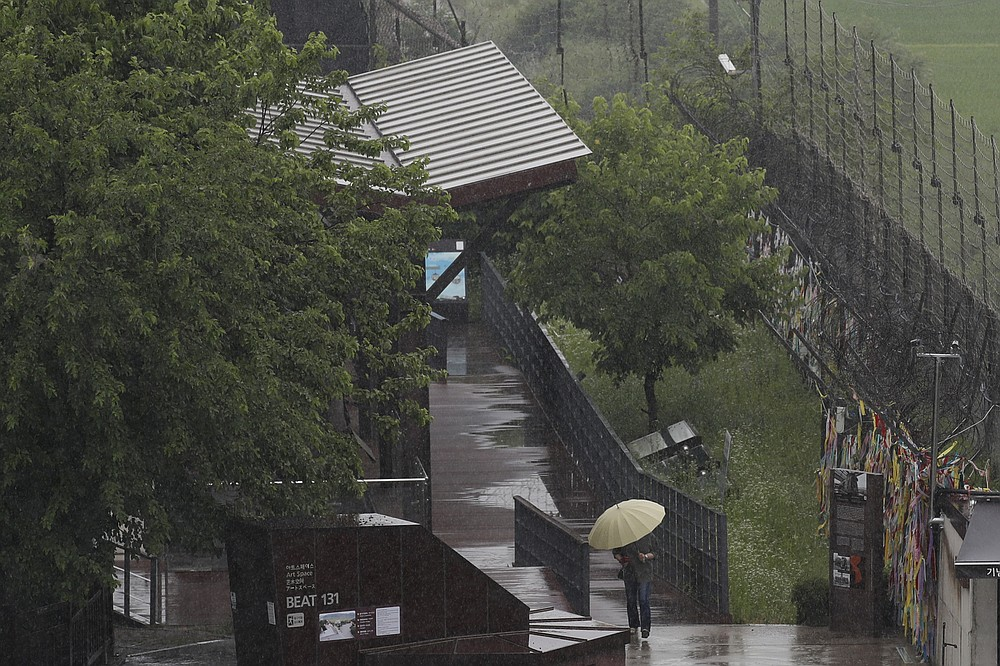 A woman holding an umbrella in rain, walks near the wire fences decorated with ribbons written with messages wishing for the reunification of the two Koreas at the Imjingak Pavilion in Paju, South Korea, Wednesday, June 24, 2020. North Korea said Wednesday leader Kim Jong Un suspended a planned military retaliation against South Korea, possibly slowing the pressure campaign it has waged against its rival amid stalled nuclear negotiations with the Trump administration. (AP Photo/Lee Jin-man)