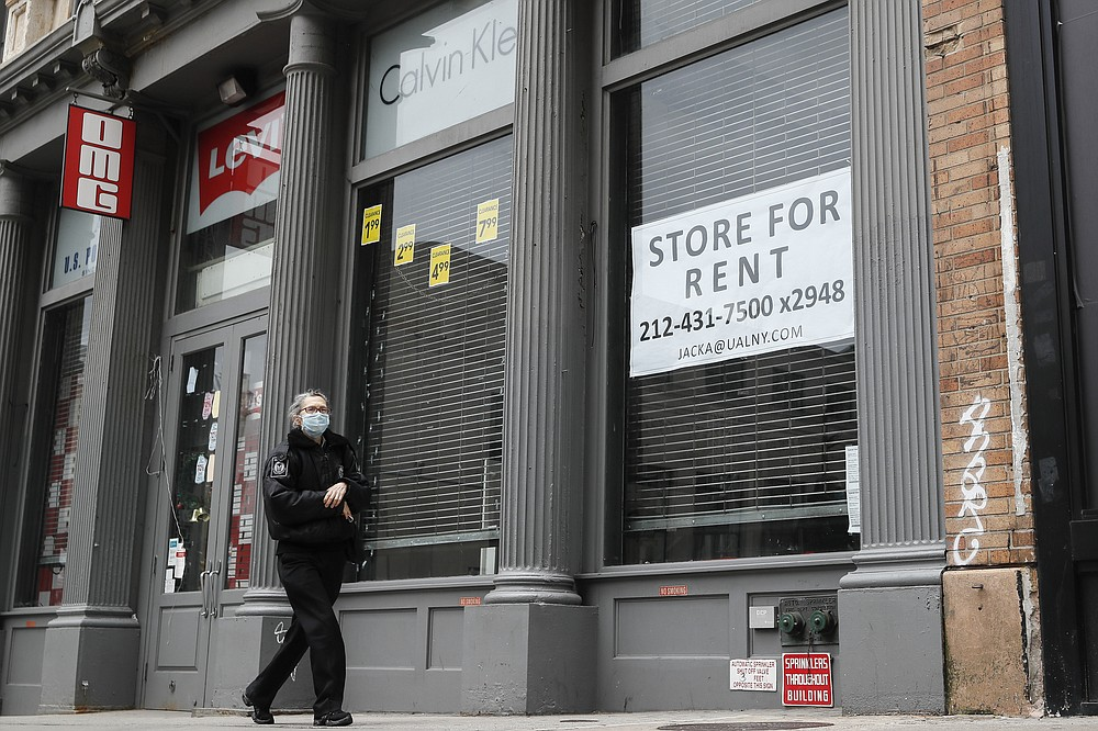 In this April 27, 2020 photo, a pedestrian passes a storefront available for rent on Broadway south of Canal Street  in the Manhattan borough of New York.  Many businesses devastated by the coronavirus pandemic are expected to abandon offices and storefronts. The changes are happening because more employees are working from home, and more people are shopping online.(AP Photo/John Minchillo)