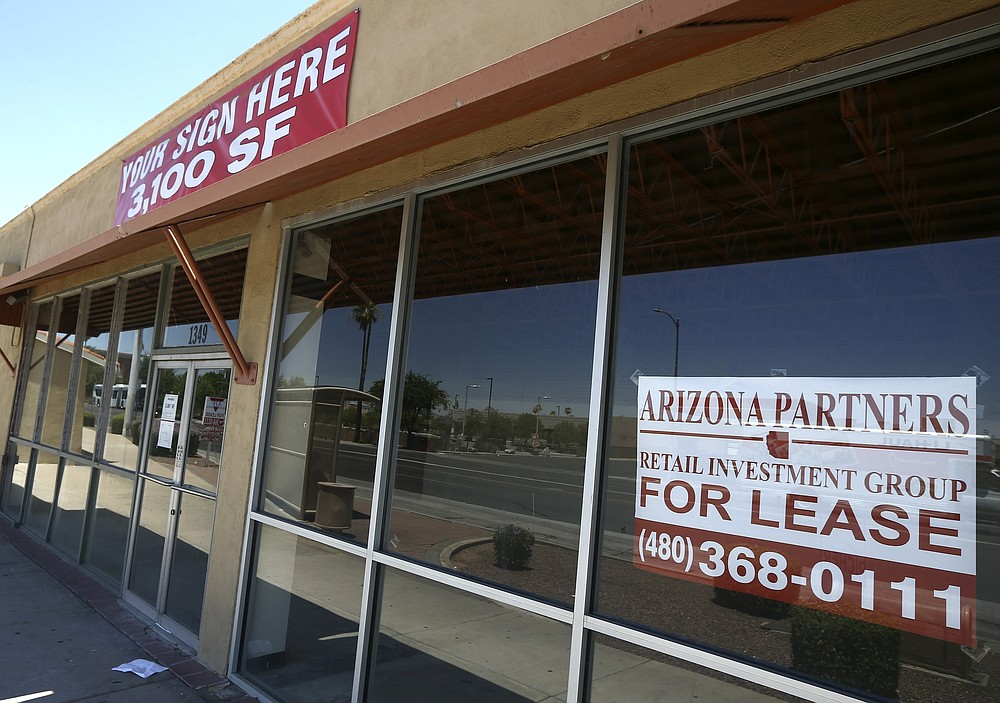 A business offers lease space available Sunday, June 21, 2020, in Phoenix.  Many businesses devastated by the coronavirus pandemic are expected to abandon offices and storefronts. The changes are happening because more employees are working from home, and more people are shopping online.(AP Photo/Ross D. Franklin)