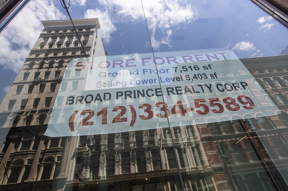In this May 7, 2020 photo, a store for rent sign hangs in the window of an empty storefront  in the Soho neighborhood of Manhattan in New York.  Many businesses devastated by the coronavirus pandemic are expected to abandon offices and storefronts. The changes are happening because more employees are working from home, and more people are shopping online. (AP Photo/Mary Altaffer)