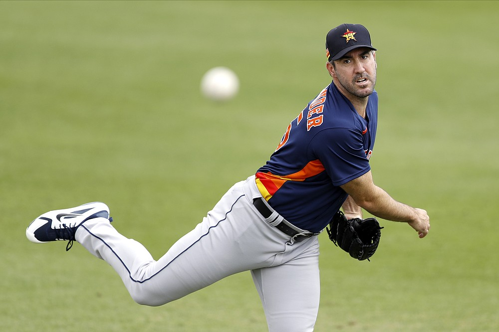 "FILE - In this March 3, 2020, file photo, Houston Astros pitcher Justin Verlander warms up prior to the team's spring training baseball game against the St. Louis Cardinals in Jupiter, Fla.  Verlander has resumed throwing as he recovers from March groin surgery. Houston manager Dusty Baker said Wednesday, April 15, that Verlander, who had surgery on March 17, is ""doing great"" and is throwing as he continues his rehabilitation. (AP Photo/Julio Cortez, File)"