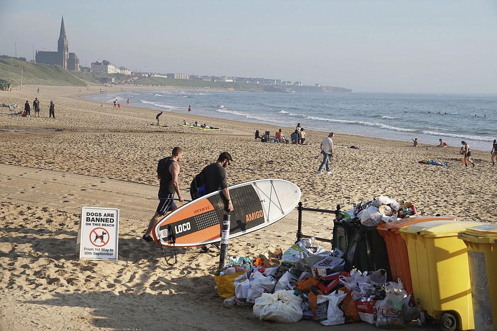 A man carrying a paddleboard passes rubbish collected by locals at Tynemouth beach after crowds gathered Thursday, in north east England, Friday June 26, 2020. British Health Secretary Matt Hancock has warned that the government has the power to close beaches and other public spaces in England amid growing concerns over the public's adherence to coronavirus social distancing rules. (Owen Humphreys/PA via AP)
