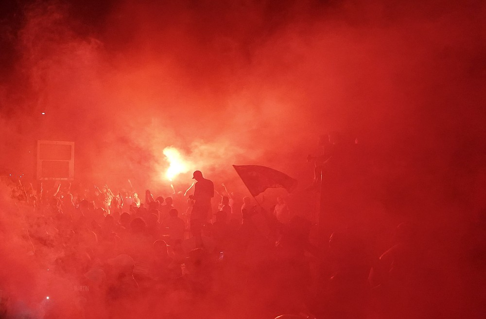 Liverpool supporters celebrate as they gather outside of Anfield Stadium in Liverpool, England, Thursday, June 25, 2020 after Liverpool clinched the English Premier League title. Liverpool took the title after Manchester City failed to beat Chelsea on Wednesday evening. (AP photo/Jon Super)