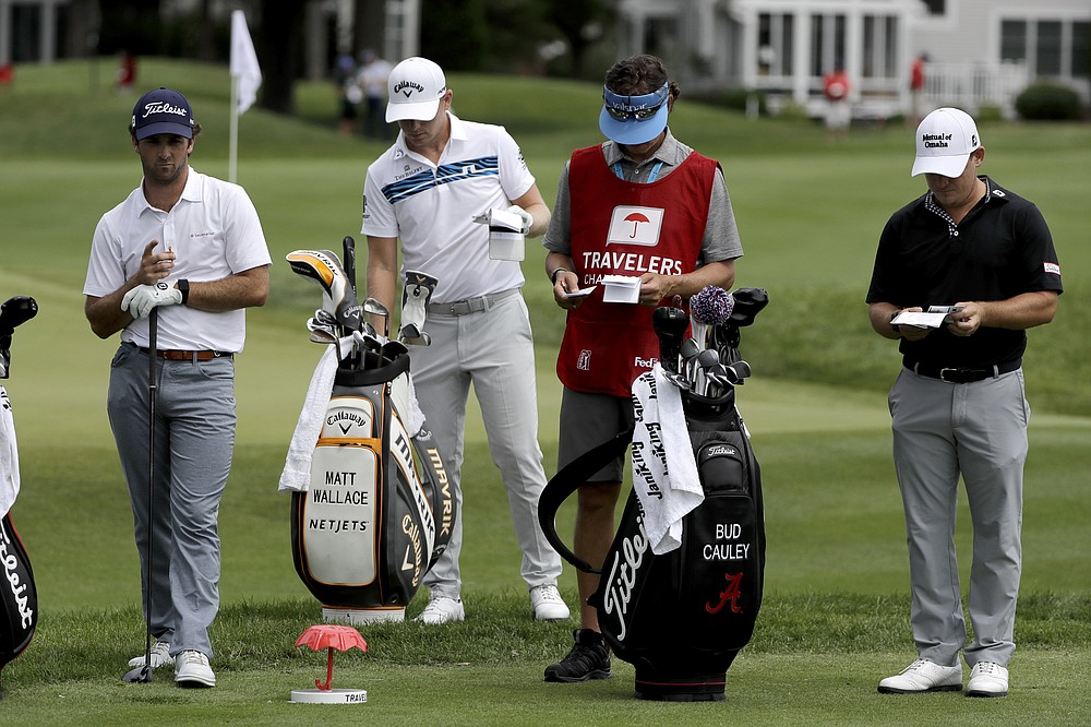 In this Thursday, June 25, photo, Denny McCarthy, left, Matt Wallace, center left, Bud Cauley, right, and Cauley's caddie Matt Hauser stand at the third tee box during the first round of the Travelers Championship golf tournament at TPC River Highlands in Cromwell, Conn. McCarthy told Golfchannel.com that he withdrew from the tournament after feeling sick Thursday night and testing positive for the coronavirus on Friday. Cauley, who played with McCarthy on Thursday, also withdrew before Friday's second round. McCarthy became the third PGA Tour player to test positive for the virus since its restart and the second this week, joining Cameron Champ who withdrew on Tuesday. Nick Watney withdrew just before the second round of last week's RBC Heritage Championship. (AP Photo/Frank Franklin II)