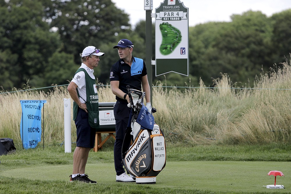 Matt Wallace, right, of England, stands with his caddie David McNeilly before teeing off on the third hole during the second round of the Travelers Championship golf tournament at TPC River Highlands, Friday, June 26, 2020, in Cromwell, Conn. Wallace is playing the second round by himself after two other golfers in his group, Denny McCarthy and Bud Cauley, withdrew from the tournament. McCarthy told Golfchannel.com that he withdrew from the tournament after feeling sick Thursday night and testing positive for the coronavirus on Friday. Cauley, who played with McCarthy on Thursday, also withdrew before Friday's second round. McCarthy became the third PGA Tour player to test positive for the virus since its restart and the second this week, joining Cameron Champ who withdrew on Tuesday. Nick Watney withdrew just before the second round of last week's RBC Heritage Championship. (AP Photo/Frank Franklin II)