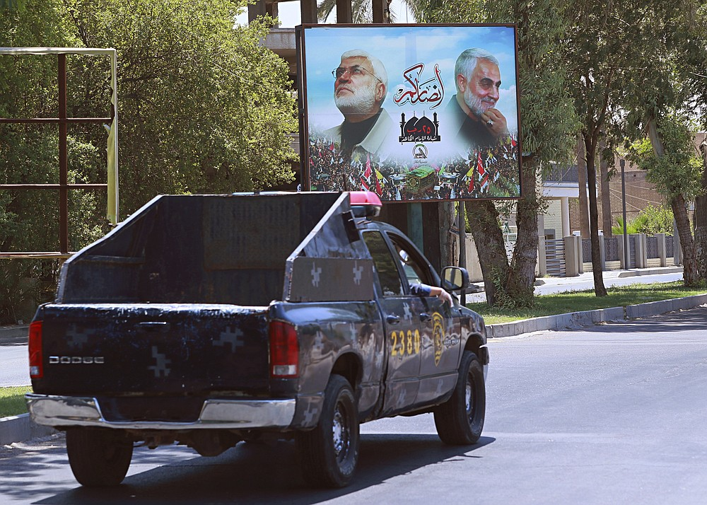 A poster of killed militia with Popular Mobilization militia is seen in Baghdad, Iraq, Friday, June 26, 2020. Iraqi security forces arrested over a dozen men suspected of a spate of rocket attacks against the U.S. (AP Photo/Hadi Mizban)