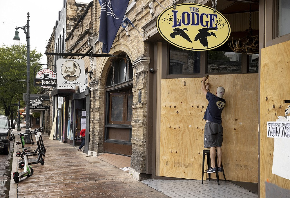 Matthew Gaskamp, General Manager of The Lodge, boards up his bar on East 6th Street in Austin, Texas, Friday, June 26, 2020, after Gov. Greg Abbott closed bars in Texas due to the coronavirus. (Jay Janner/Austin American-Statesman via AP)
