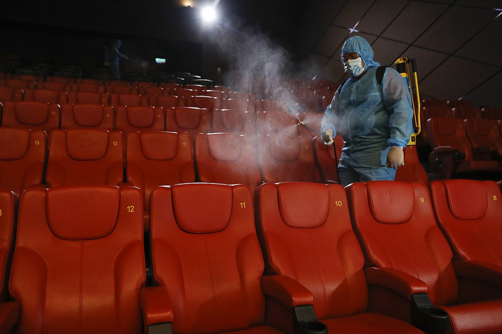 A staff member of a cinema sprays disinfectant at the cinema hall to prepare for reopening on July 1 in Kuala Lumpur, Malaysia, Friday, June 26, 2020. Malaysia entered the Recovery Movement Control Order (RMCO) after three months of coronavirus restrictions. (AP Photo/Vincent Thian)