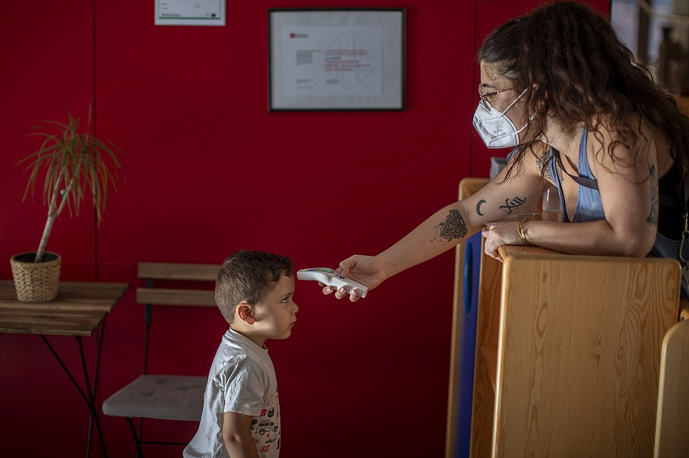 Hugo, 3, has his temperature taken by a teacher as he arrives at Cobi kindergarten in Barcelona, Spain, Friday, June 26, 2020. Spain's cabinet will extend the furlough schemes adopted during the coronavirus lockdown that brought the economy to a standstill until the end of September. (AP Photo/Emilio Morenatti)