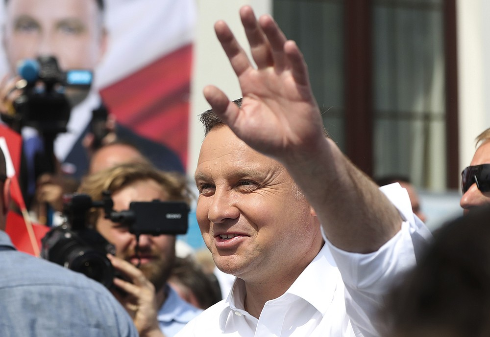 Polish President Andrzej Duda waves to supporters as he campaigns for a second term in Serock, Poland, on Wednesday, June 17, 2020, Duda is the frontrunner ahead of the election on Sunday, June 28, but is not expected to reach the 50% threshold needed to win outright. That will require a runoff two weeks later in which he is expected to face off against Warsaw Mayor Rafal Trzaskowski in a very close race.(AP Photo/Czarek Sokolowski)