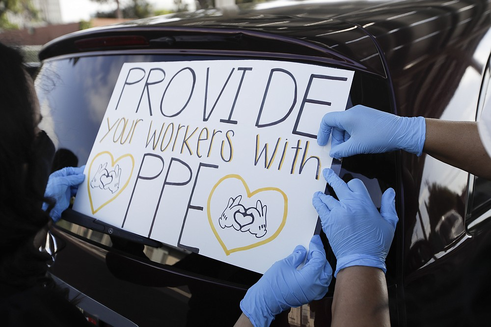 Signs are taped to a car before the start of a drive-by protest by Disney employees to demand a safe reopening amid the coronavirus pandemic Saturday, June 27, 2020, in Anaheim, Calif. Workers are demanding regular testing, stricter cleaning protocols and higher staffing levels. Disney had originally proposed reopening on July 17th but announced this week it was postponing. (AP Photo/Marcio Jose Sanchez)