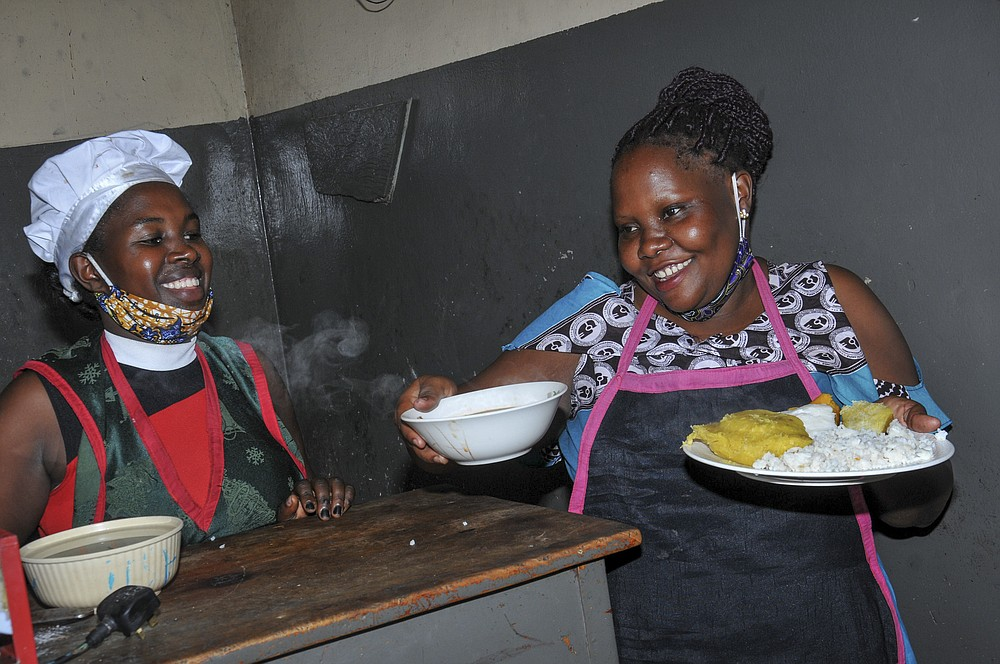 In this photo taken Saturday, June 20, 2020, Rebecca Nakamanya, left, and colleague Namara Grace, right, work at a restaurant near a bus terminal in capital Kampala, Uganda. The COVID-19 pandemic means that millions of women in Africa and other developing regions could lose years of success in contributing to household incomes, asserting their independence and expanding financial inclusion. (AP Photo/Ronald Kabuubi)