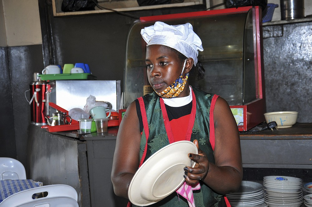 In this photo taken Saturday, June 20, 2020, Rebecca Nakamanya works at a restaurant near a bus terminal in capital Kampala, Uganda. The COVID-19 pandemic means that millions of women in Africa and other developing regions could lose years of success in contributing to household incomes, asserting their independence and expanding financial inclusion. (AP Photo/Ronald Kabuubi)
