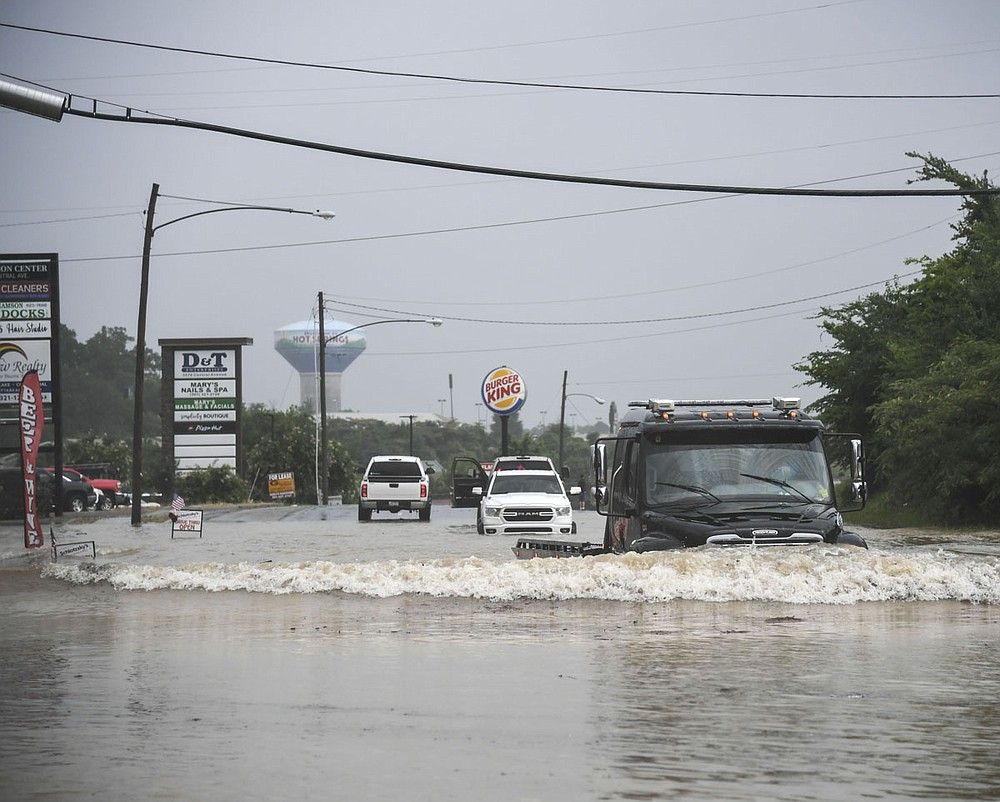 A tow truck drives through a flooded stretch of road in the 3500 block of Central Avenue Monday afternoon. - Photo by Grace Brown of The Sentinel-Record