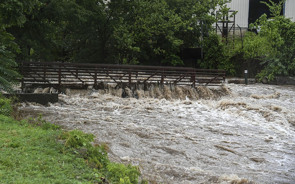 Hot Springs Creek rushes over a bridge behind the Valley Street Skatepark on Monday. - Photo by Grace Brown of The Sentinel-Record