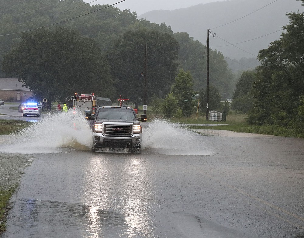 A truck leaves a flooded area of Mountain Pine near the railroad tracks and entrance to the town following heavy rains on Monday. - Photo by Richard Rasmussen of The Sentinel-Record