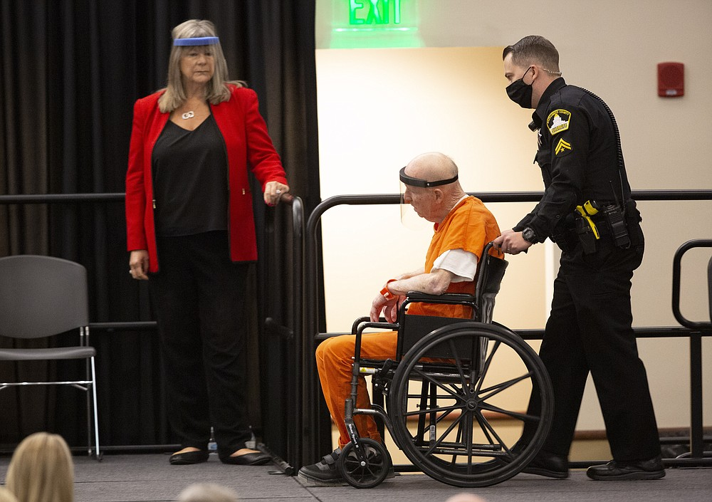 Joseph James DeAngelo, charged with being the Golden State Killer, is wheeled into the courtroom as his attorney, public defender Diane Howard, left, looks on in Sacramento, Calif., Monday June 29, 2020. DeAngelo, 74, pleaded guilty to multiple counts of murder and other charges 40 years after a sadistic series of assaults and slayings in California. Due to the large numbers of people attending, the hearing was held at a ballroom at California State University, Sacramento to allow for social distancing. (AP Photo/Rich Pedroncelli)