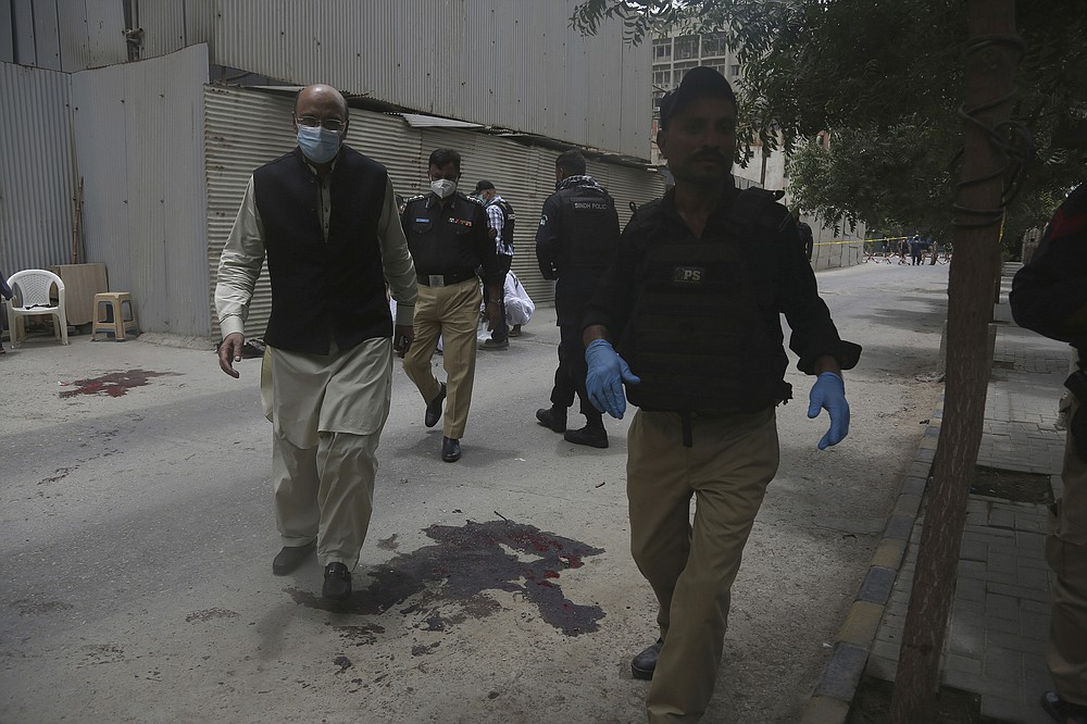 Police officers head to the Stock Exchange Building in Karachi, Pakistan, Monday, June 29, 2020. Gunmen have attacked the stock exchange in the Pakistani city of Karachi on Monday. Special police forces deployed to the scene of the attack and in a swift operation secured the building. (AP Photo/Fareed Khan)