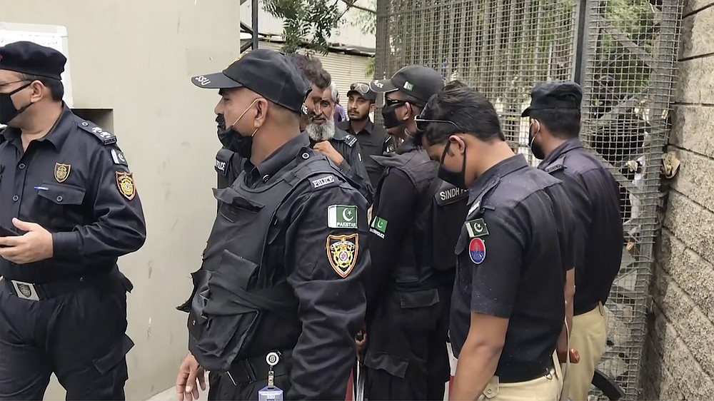 In this image made from a video, police stand around an entrance of stock exchange building in Karachi, Pakistan Monday, June 29, 2020. Militants attacked the stock exchange in the Pakistani city of Karachi on Monday, according to police. (AP Photo)