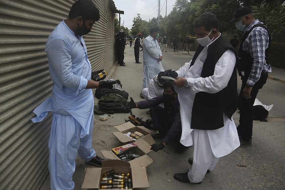 Security personnel examine confiscated ammunition from attackers outside the Stock Exchange Building in Karachi, Pakistan, Monday, June 29, 2020. Gunmen have attacked the stock exchange in the Pakistani city of Karachi on Monday. Special police forces deployed to the scene of the attack and in a swift operation secured the building. (AP Photo/Fareed Khan)