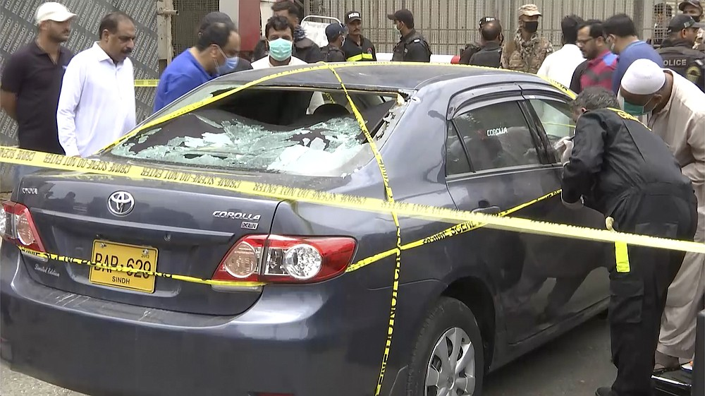 In this image made from a video, police and investigators gather around a car used by attackers, in Karachi, Pakistan Monday, June 29, 2020. Militants attacked the stock exchange in the Pakistani city of Karachi on Monday, according to police. (AP Photo)