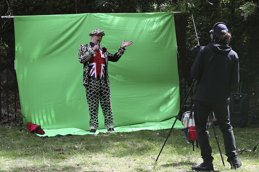 Entertainer Mickie Driver performs in front of a green screen background at a park in London Monday June 29, 2020 as he is filmed making a promotional video in support of buskers and street musicians whose livelihood was affected by the coronavirus lockdown. (AP Photo/Tony Hicks)