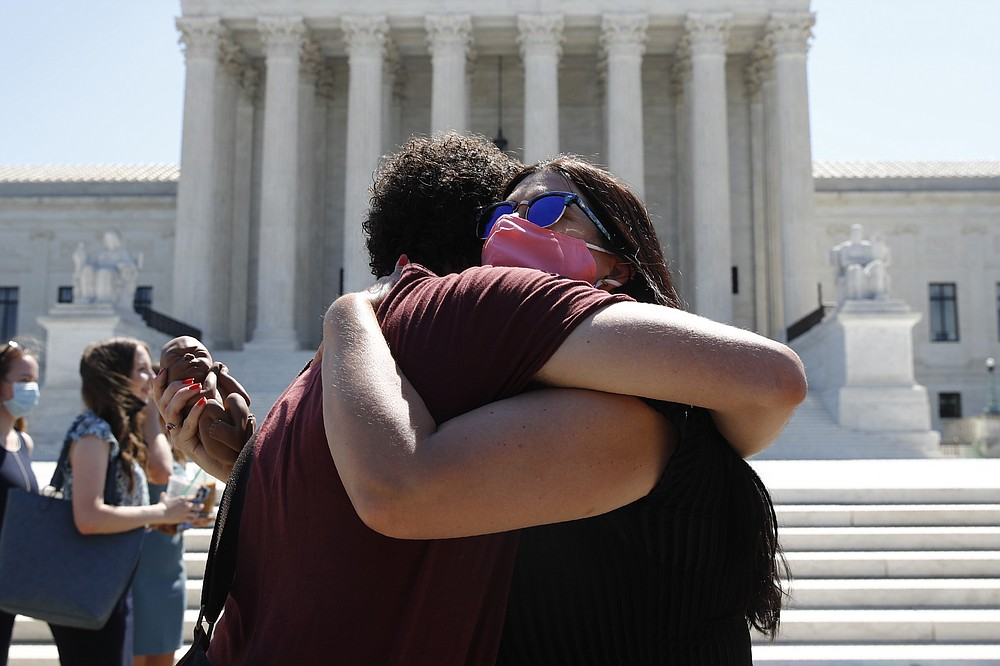Anti-abortion protesters hug goodbye outside the Supreme Court on Capitol Hill in Washington, Monday, June 29, 2020.  The Supreme Court has struck down a Louisiana law regulating abortion clinics, reasserting a commitment to abortion rights over fierce opposition from dissenting conservative justices in the first big abortion case of the Trump era. (AP Photo/Patrick Semansky)