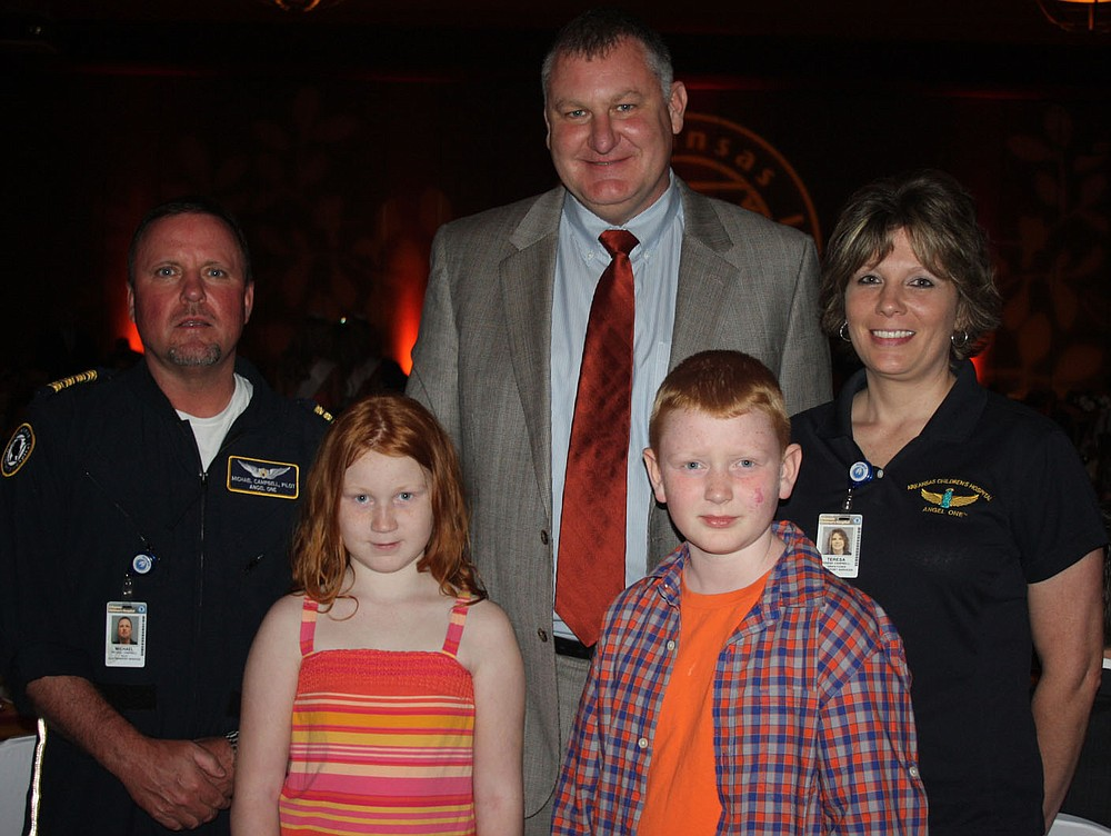 STAFF PHOTO CARIN SCHOPPMEYER Mike Campbell, Angel 1 pilot, from left, Jenna Wilson, David Wilson, Ethan Wilson and Teresa Campbell, Angel 1 dispatcher, attend the Color of Hope Gala to benefit Arkansas Children's Hospital on Aug. 24. Ethan was the 2013 Color of Hope Champion Child.