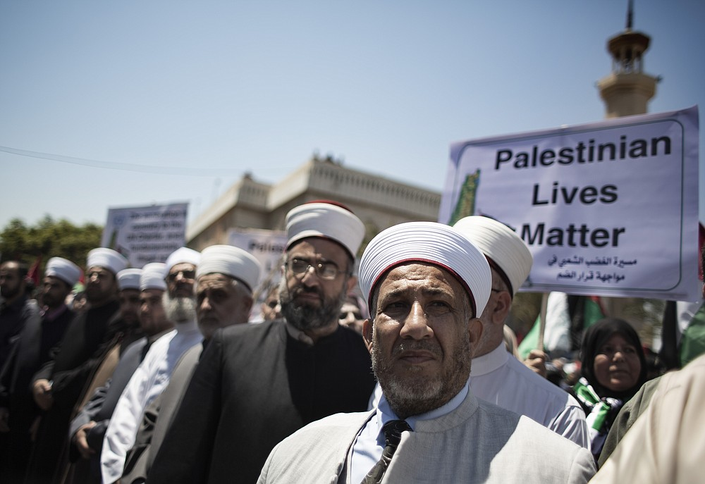 Palestinian Muslim clerics attend a demonstration against Israeli plans for the annexation of parts of the West Bank, in Gaza City, Wednesday, July 1, 2020. (AP Photo/Khalil Hamra)