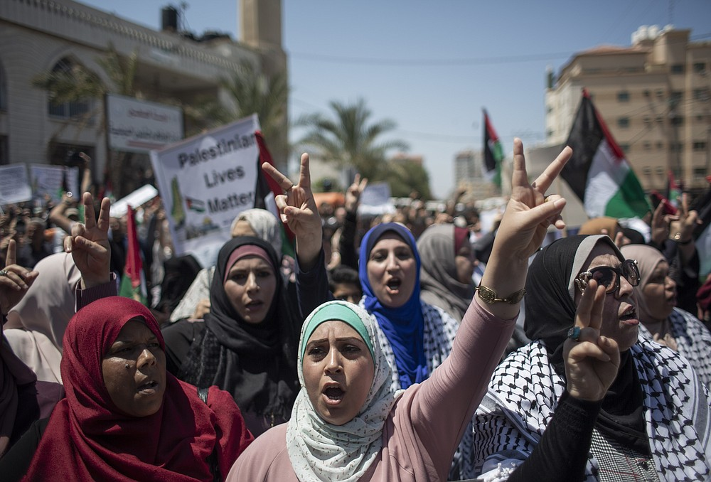 Palestinian women chant slogans and flash victory signs as they demonstrate against Israeli plans for the annexation of parts of the West Bank, in Gaza City, Wednesday, July 1, 2020. (AP Photo/Khalil Hamra)