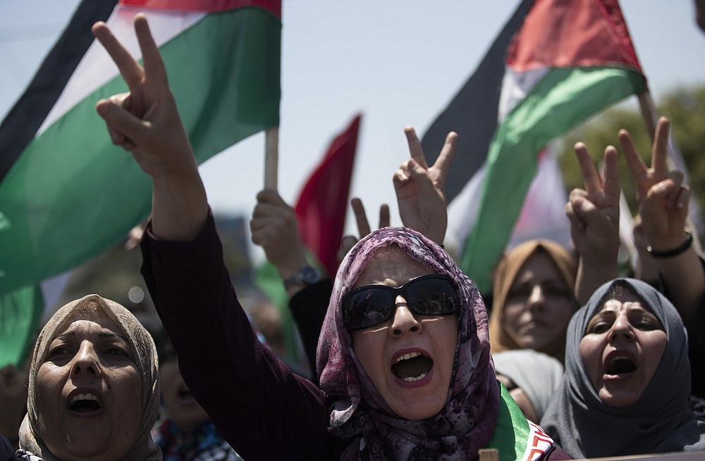 Palestinian women chant slogans and flash the victory sign as they demonstrate against Israeli plans for the annexation of parts of the West Bank, in Gaza City, Wednesday, July 1, 2020. (AP Photo/Khalil Hamra)
