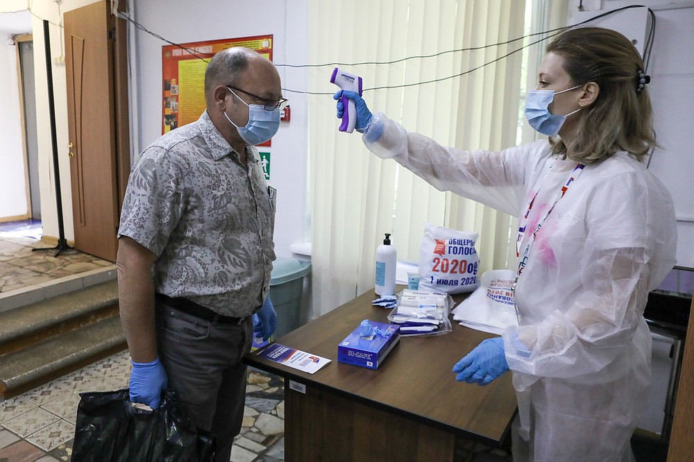 A member of election commission, right, checks the temperature of a voter, both wearing face masks to protect against coronavirus at a polling station in Moscow, Russia, Wednesday, July 1, 2020. The vote on the constitutional amendments that would reset the clock on Russian President Vladimir Putin's tenure and enable him to serve two more six-year terms is set to wrap up Wednesday. (Sofia Sandurskaya, Moscow News Agency photo via AP)