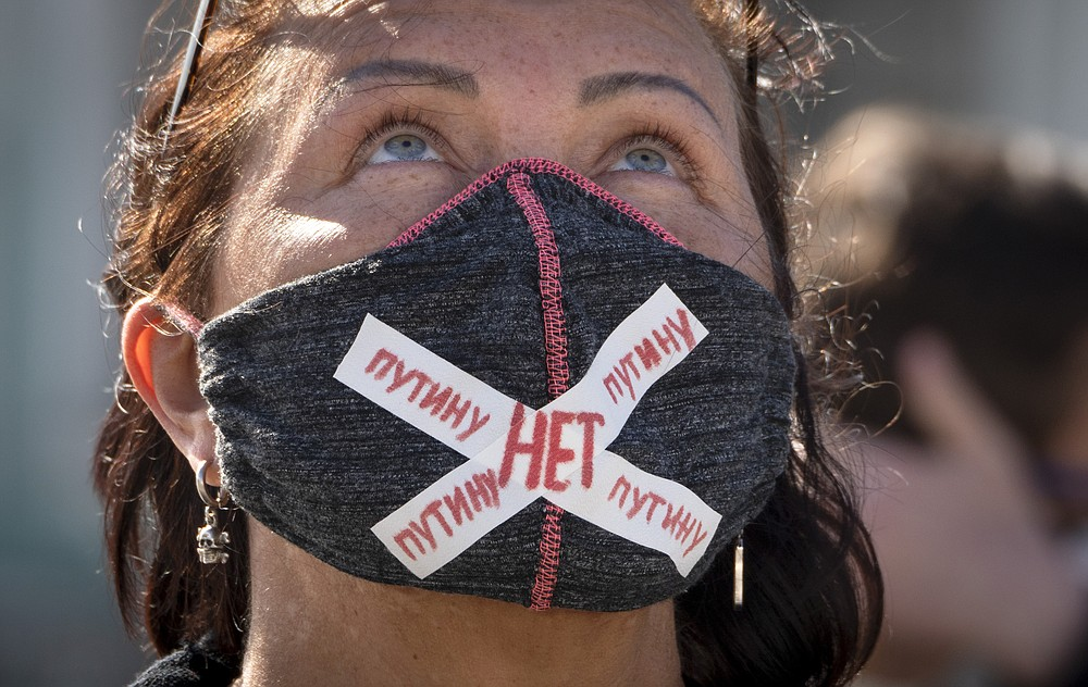 """A woman wears a face mask to protect against coronavirus infection with a sign """"No to Putin"""" during a protest against constitutional amendments at the Palace Square in St.Petersburg, Russia, Wednesday, July 1, 2020. The vote on the constitutional amendments that would reset the clock on Russian President Vladimir Putin's tenure and enable him to serve two more six-year terms is set to wrap up Wednesday. (AP Photo/Dmitri Lovetsky)"""