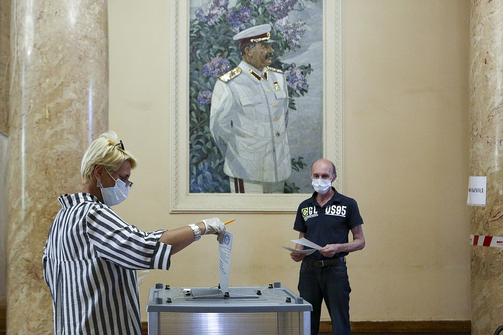 A woman, wearing a face mask and gloves to protect against coronavirus and observing social distancing guidelines, casts her ballot at a polling station with a portrait of former Soviet leader Josef Stalin on the wall in Volgograd, former Stalingrad, Russia, Wednesday, July 1, 2020. The vote on the constitutional amendments that would reset the clock on Russian President Vladimir Putin's tenure and enable him to serve two more six-year terms is set to wrap up Wednesday. (AP Photo/Dmitry Rogulin)