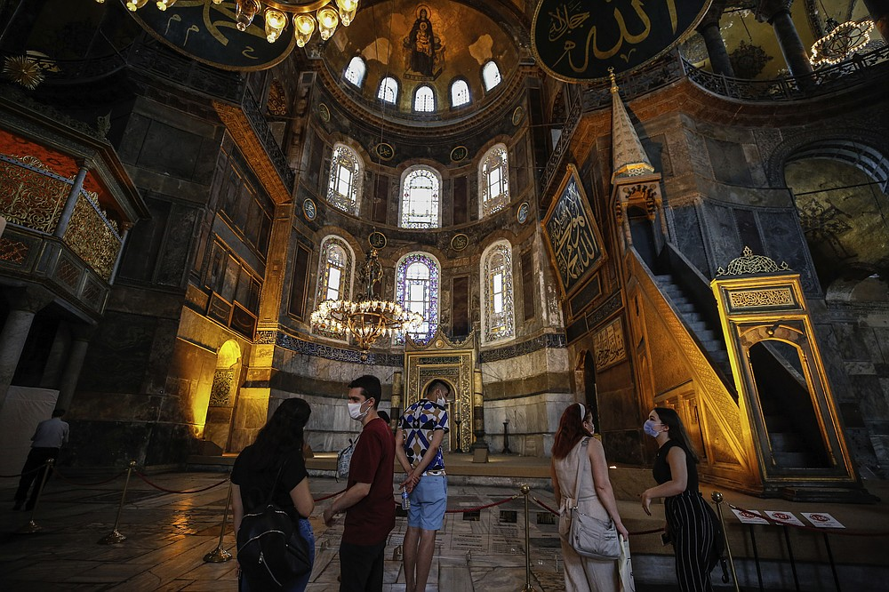 People visit the Byzantine-era Hagia Sophia, one of Istanbul's main tourist attractions in the historic Sultanahmet district of Istanbul on Thursday, June 25, 2020. The 6th-century building is now at the center of a heated debate between conservative groups who want it to be reconverted into a mosque and those who believe the World Heritage site should remain a museum. (AP Photo/Emrah Gurel)
