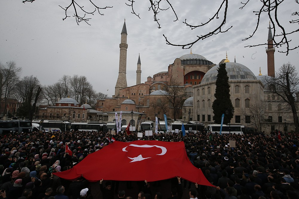 FILE - In this Saturday, March 16, 2019 file photo, backdropped by Hagia Sophia, the Byzantine-era cathedral that was turned into a mosque and now serves as a museum, demonstrators protest holding a Turkish flag. The 6th-century building is now at the center of a heated debate between conservative groups who want it to be reconverted into a mosque and those who believe the World Heritage site should remain a museum. (AP Photo/Lefteris Pitarakis, File)