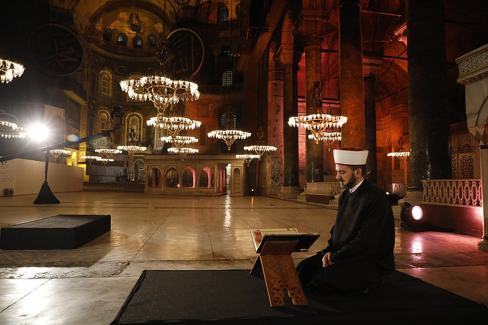 """FILE - In this Friday, May 29, 2020 file photo, a Muslim cleric recites the """"prayer conquest"""" from the Quran, Islam's holy book, inside Istanbul's 6th-century Hagia Sophia — the main cathedral of the Byzantine Empire which was converted into a mosque with the Ottoman conquest of the city, then known as Constantinople, in 1453, in Istanbul. The 6th-century building is now at the center of a heated debate between conservative groups who want it to be reconverted into a mosque and those who believe the World Heritage site should remain a museum. (AP Photo)"""