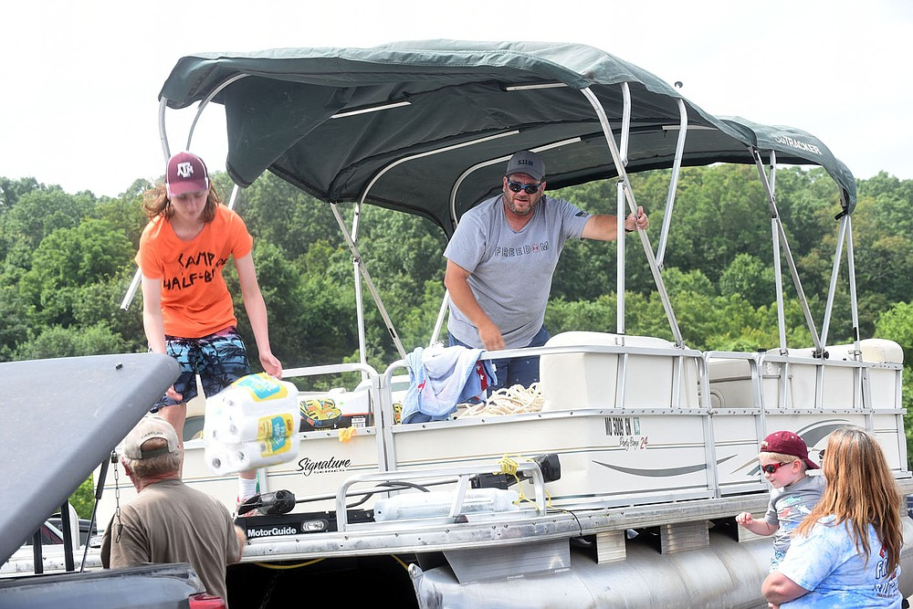 Dwayne Frantz, visiting the area from Texas, raises the canopy on a pontoon boat Wednesday for a family outing on Beaver Lake, launching at Prairie Creek park. The crew said they were getting on the water ahead of the holiday weekend rush. (NWA Democrat-Gazette/Flip Putthoff)
