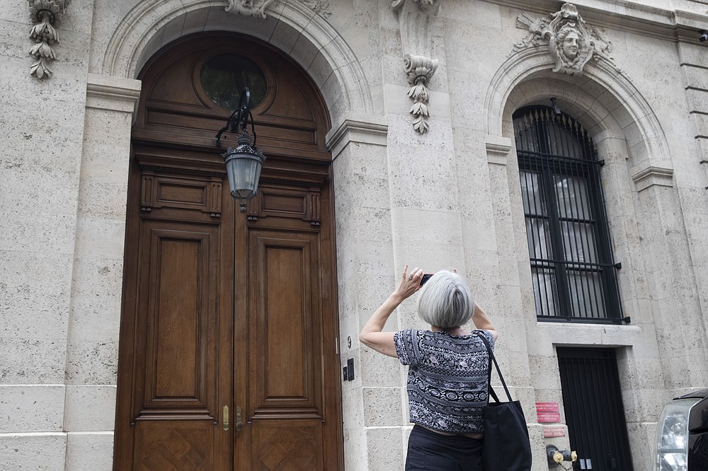 FILE - In this Aug. 13, 2019 file photo, a pedestrian stops to take a photo of Jeffrey Epstein's townhouse on the Upper East Side of Manhattan, in New York.  On Thursday July 2, 2020, the FBI arrested Ghislaine Maxwell, a British socialite who was accused by many women of helping procure underage sex partners for Epstein. The court papers said Epstein's abuse of girls occurred at his Manhattan mansion and other residences in Palm Beach, Florida; Sante Fe, New Mexico and London.  (AP Photo/Mary Altaffer, File)