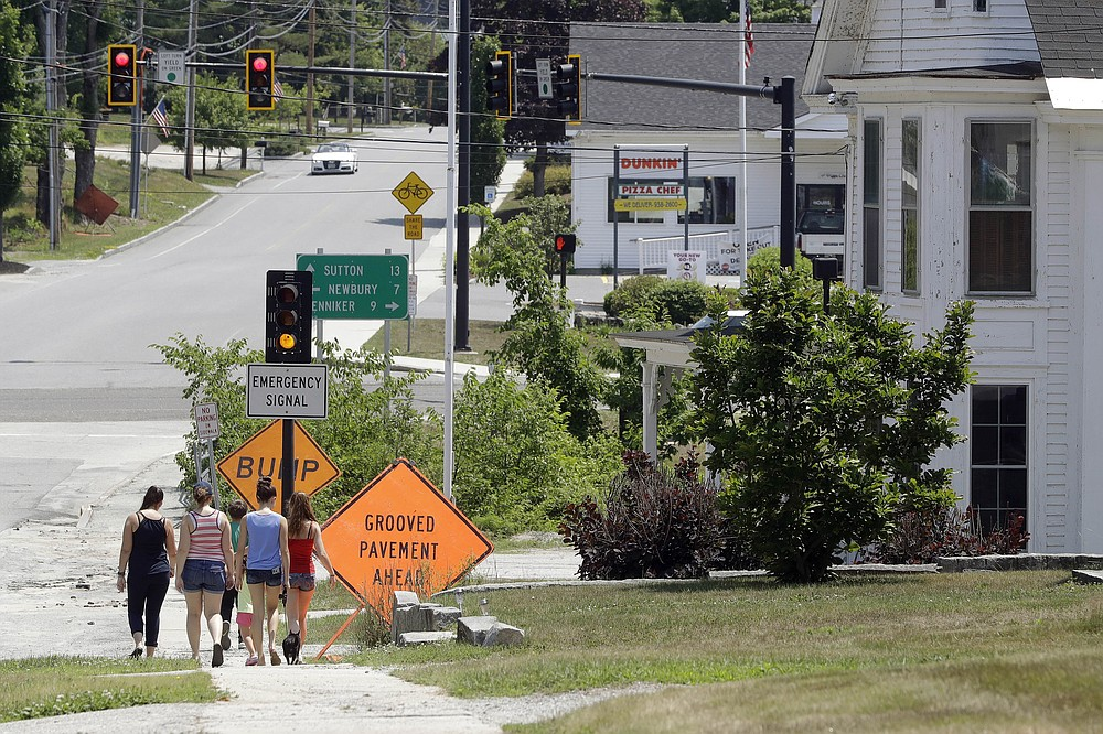 People walk through downtown Bradford, N.H., on Thursday, July 2, 2020, the small New Hampshire town where Ghislaine Maxwell, a British socialite accused by many women of helping procure underage sex partners for Jeffrey Epstein, was arrested Thursday. (AP Photo/Steven Senne)