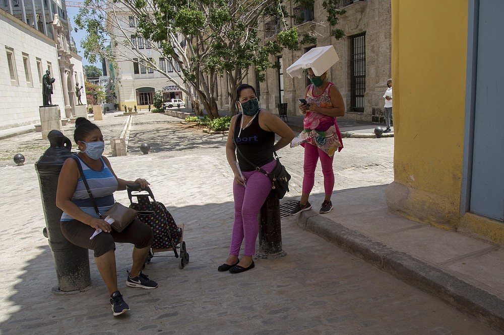 Women wearing masks to curb the spread of the new coronavirus chat on a corner in Old Havana, one using a piece of styrofoam to shade herself, in Havana, Cuba, Tuesday, June 23, 2020. All of Cuba has moved to phase one with the exception of Havana, the capital of 2 million people where the small number of new daily cases of COVID-19 has been concentrated. (AP Photo/Ismael Francisco)