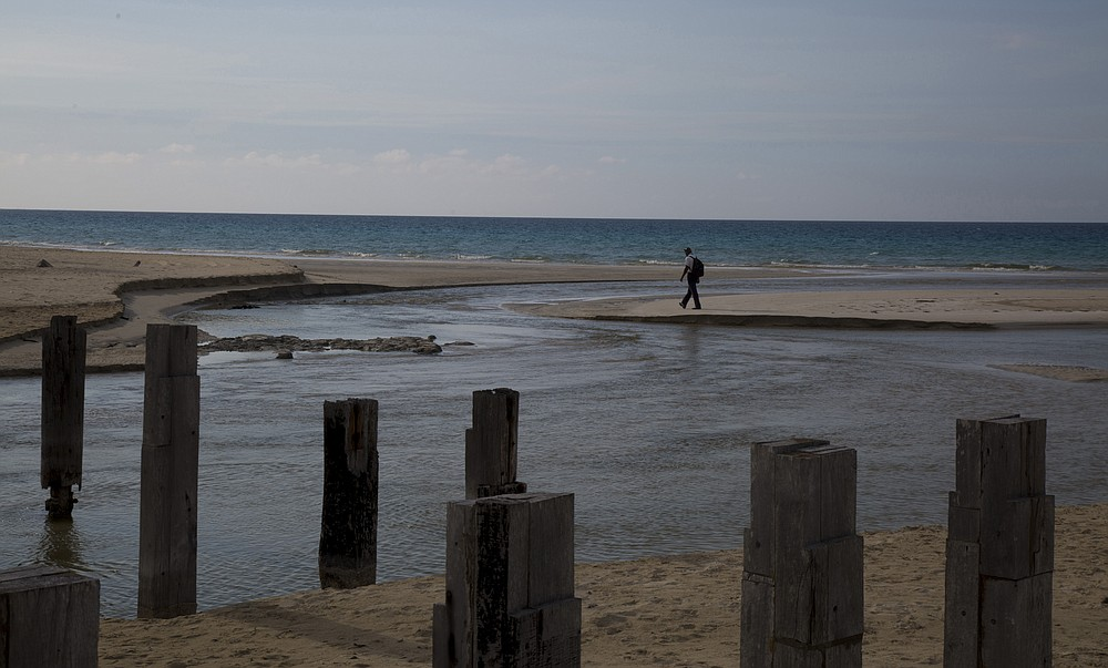 A man walks on Boca Ciega beach where swimming is restricted due to the COVID-19 pandemic in Havana, Cuba, Monday, June 22, 2020. With coronavirus cases down to a handful a day,  Cuba is betting on a new form of tourism by designating five keys off its coast as all-inclusive vacation sites almost completely isolated from the rest of Cuba, in an attempt to restart a vital industry without reintroducing the virus to the country. (AP Photo/Ismael Francisco)