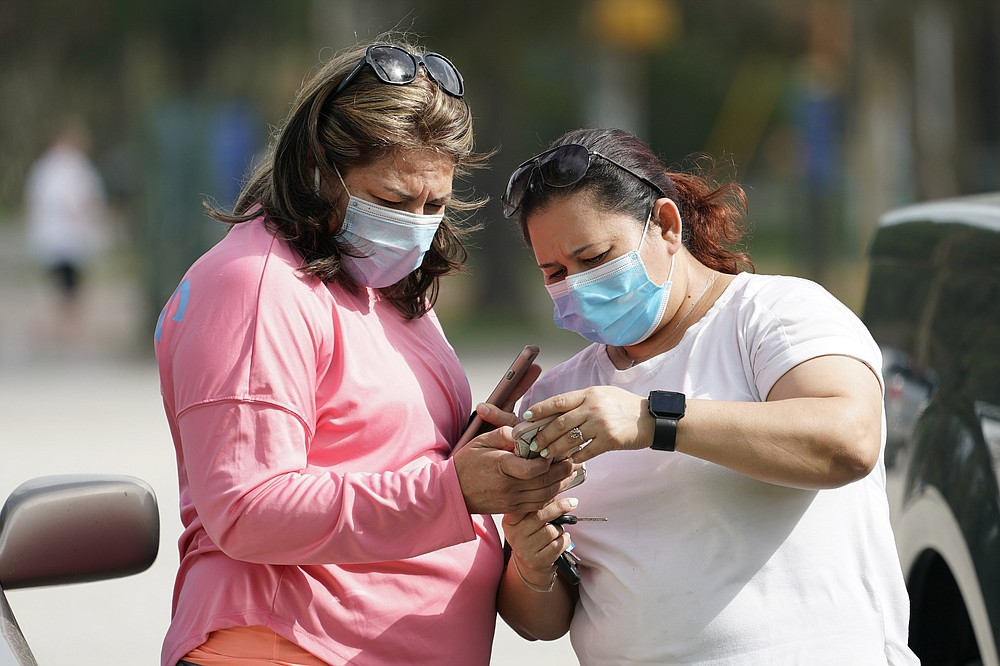 Women wear masks as they check a mobile phone Wednesday, July 1, 2014, in Houston. Harris County Commissioners have voted to extend the recently-issued mask order until August 26. The order directs any businesses providing goods or services to require all employees and visitors to wear face coverings in areas of close proximity to co-workers or the public. (AP Photo/David J. Phillip)