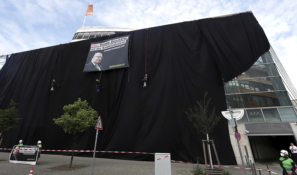 Activists of Greepeace have covered the headquarters of German Chancellor Angela Merkel's Cristian Democratic Party (CDU) with black panels to protest against the party's coal policy in Berlin, Germany, Wednesday, July 1, 2020. (AP Photo/Michael Sohn)