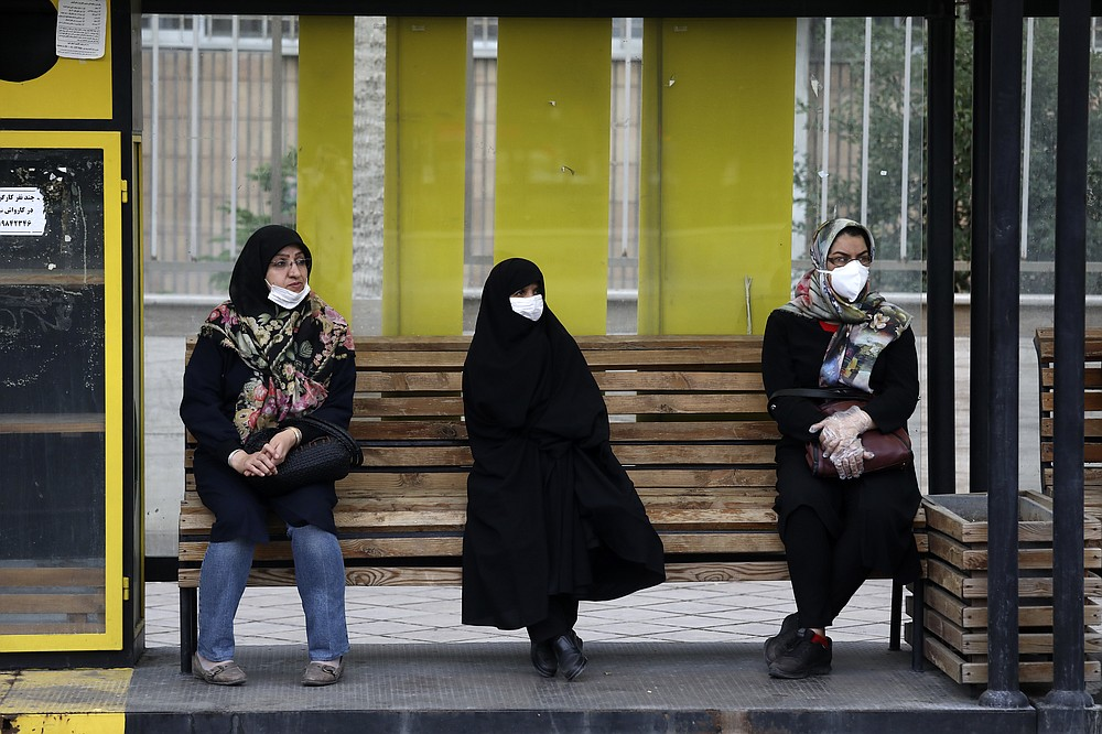 People wearing protective face masks to help prevent the spread of the coronavirus sit at a bus stop in the city of Zanjan, some 330 kilometers (205 miles) west of the capital Tehran, Iran, Sunday, July 5, 2020. Iran on Sunday instituted mandatory mask-wearing as fears mount over newly spiking reported deaths from the coronavirus, even as its public increasingly shrugs off the danger of the COVID-19 illness it causes. (AP Photo Vahid Salemi)