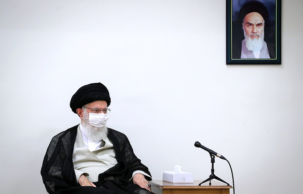 In this picture released by an official website of the office of the Iranian supreme leader on June 31, 2020, Supreme Leader Ayatollah Ali Khamenei wears a protective face mask to help prevent to spread of the coronavirus while sitting under a portrait of the late revolutionary founder Ayatollah Khomeini during a meeting in Tehran, Iran. Iran on Sunday instituted mandatory mask-wearing as fears mount over newly spiking reported deaths from the coronavirus, even as its public increasingly shrugs off the danger of the COVID-19 illness it causes. Khamenei has publicized an image of himself in a mask in recent days, urging both public officials and the Islamic Republic's 80 million people to wear them to stop the virus's spread. (Office of the Iranian Supreme Leader via AP)