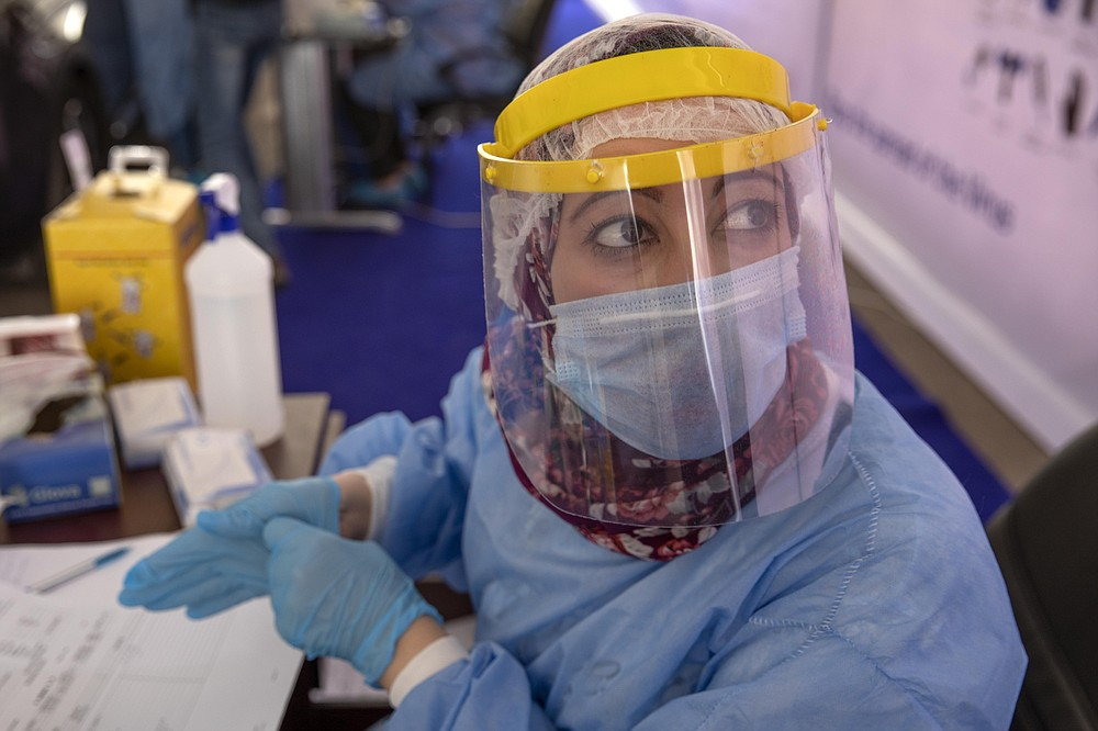 FILE - In this June 17, 2020 file photo, a health worker wearing protective gear prepares to take swab samples from people lining up in their cars to test for the coronavirus at a drive-through COVID-19 screening center at Ain Shams University in Cairo, Egypt. Coronavirus infections are surging in the country of 100 million, threatening to overwhelm hospitals. (AP Photo/Nariman El-Mofty, File)
